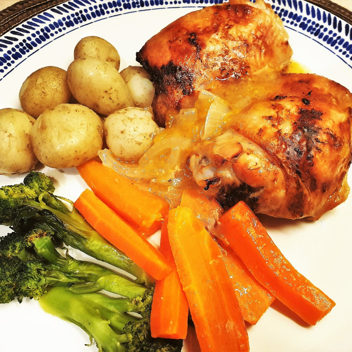 A plate of orange chicken thighs with potatoes, carrots and broccoli.