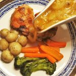 Chicken thighs and vegetables on a plate, with sauce being poured over.