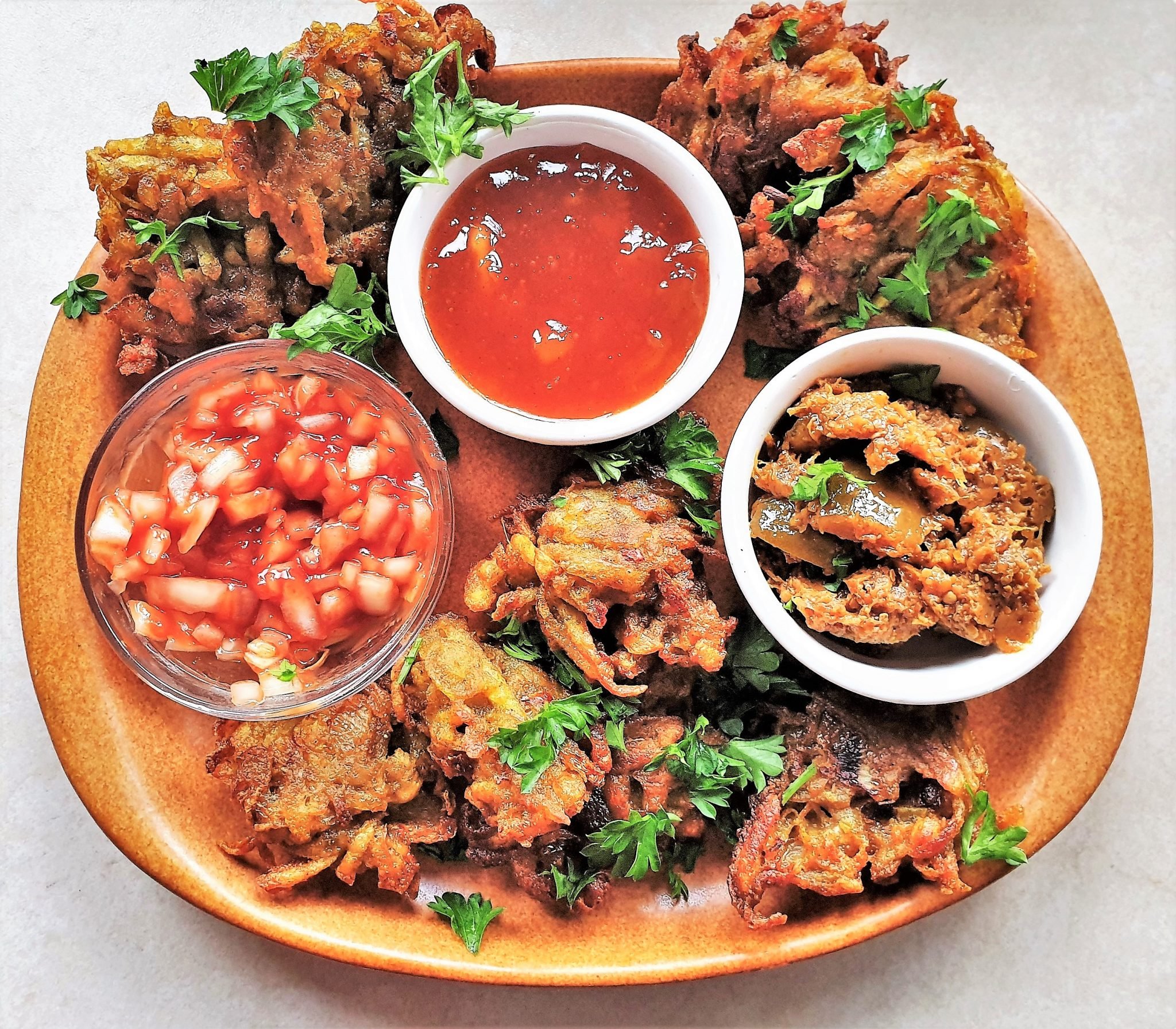 A plate of potato and onion bhajis with dipping sauces.
