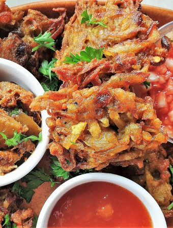 Close up of a potato and onion bhaji with dipping sauces.