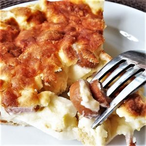 A slice of savoury tart on a plate with a fork.