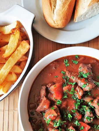 A bowl of beef trinchado next to a bowl of french fries.
