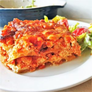 A slice of turkey and ham lasagne on a white plate.