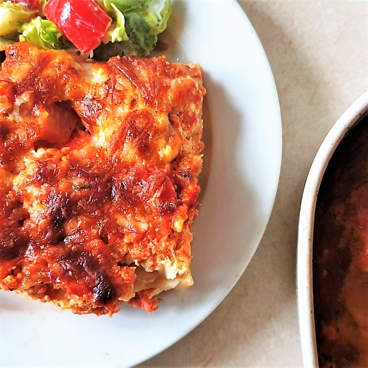 A slice of turkey and ham lasagne on a plate with a salad.