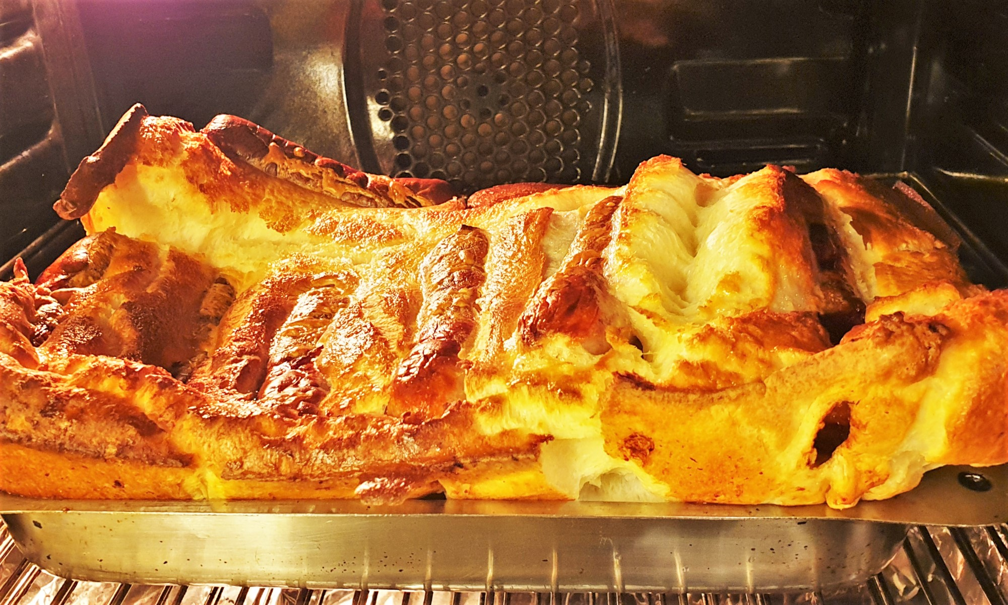 A dish of toad in the hole baking in the oven.