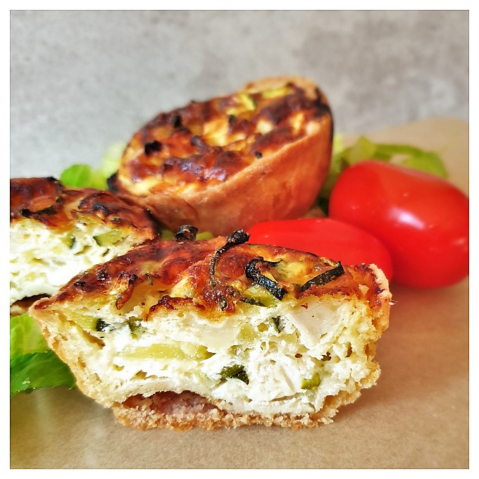 Zucchini and goat cheese tarts on a plate with tomatoes.