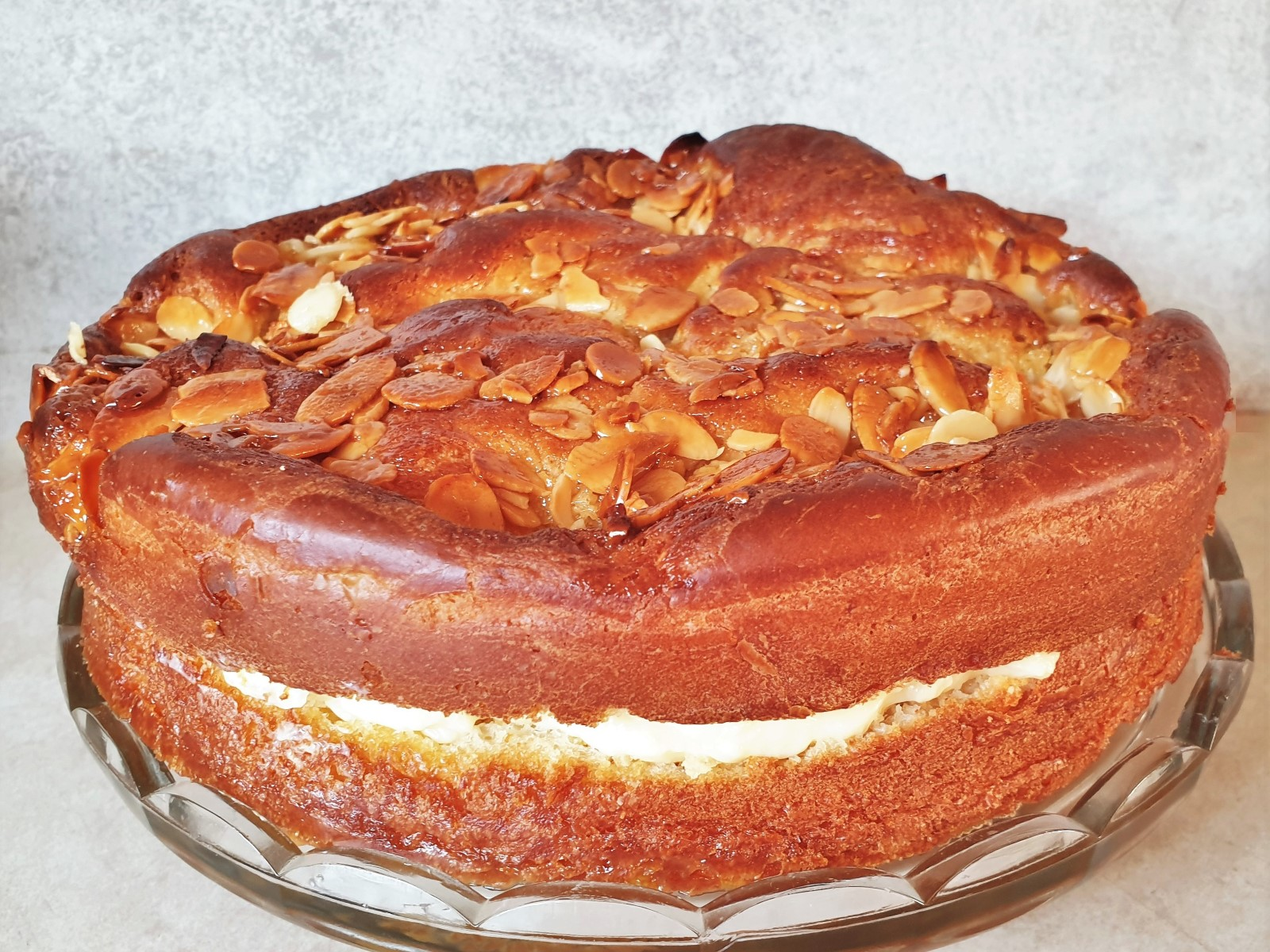 An side on view of a bee sting cake showing the rise of the cake, the filling and the crunch almond topping.