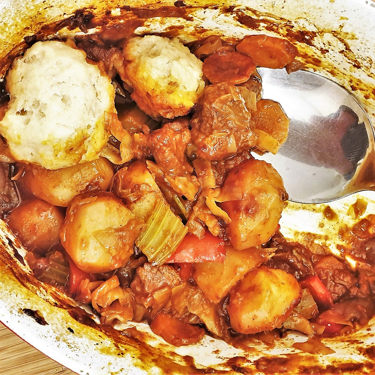 Closeup of the beef casserole and suet dumplings being spooned from the dish.