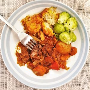 A plate of beef casserole with suet dumplings, showing a fork cutting into the beef, with fluffy dumplings and the first brussels sprouts of the season.