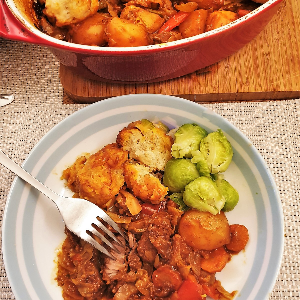 A dish of beef casserole and suet dumplings with a side helping of brussels sprouts.