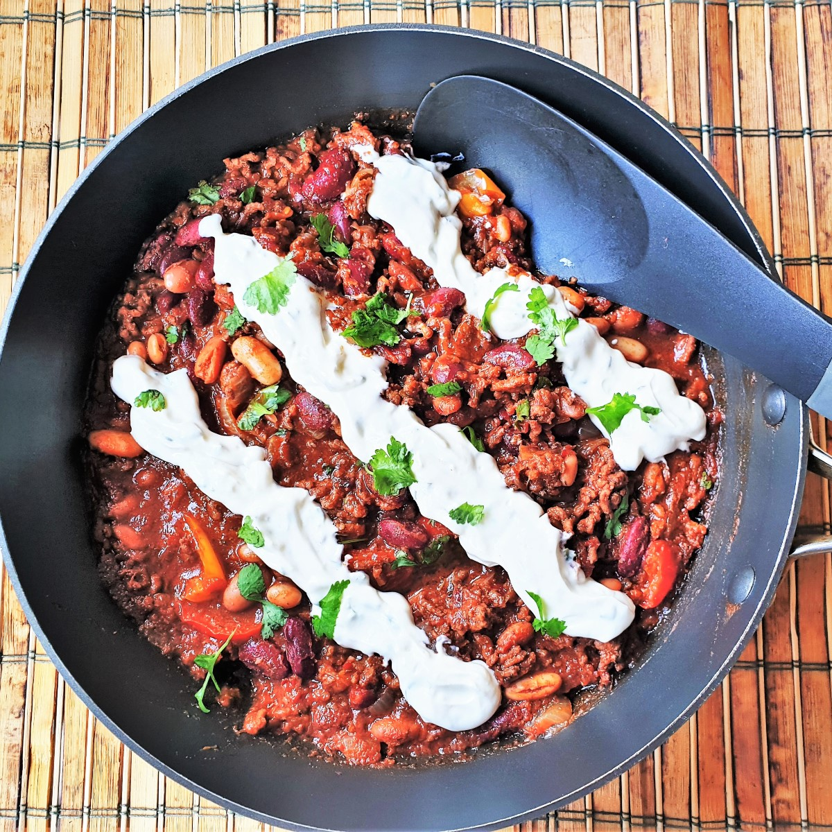 A pan of chilli with 3 rows of sour cream piped on top.