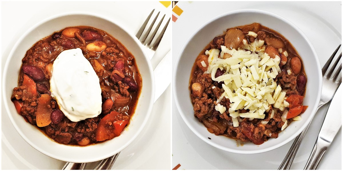 Two bowls of chilli, one topped with sour cream and the other topped with grated cheese.
