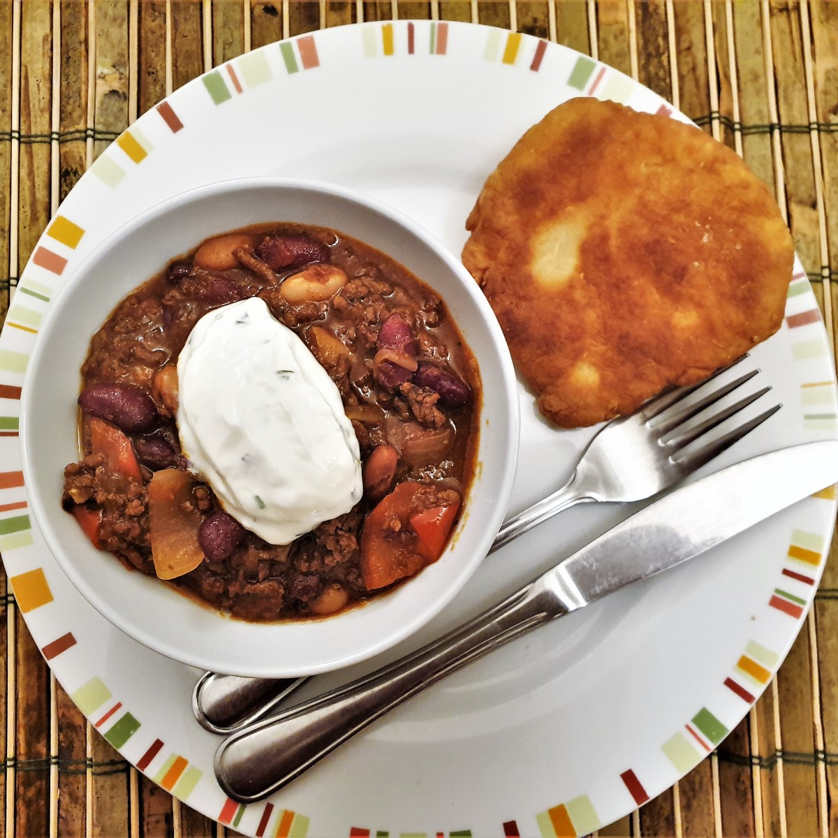A bowl of chillli con carne topped with sour cream, alongside a homemade vetkoek (or fried dough ball).