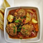 A dish of meatball soup with vegetables and tomatoes and custy bread.