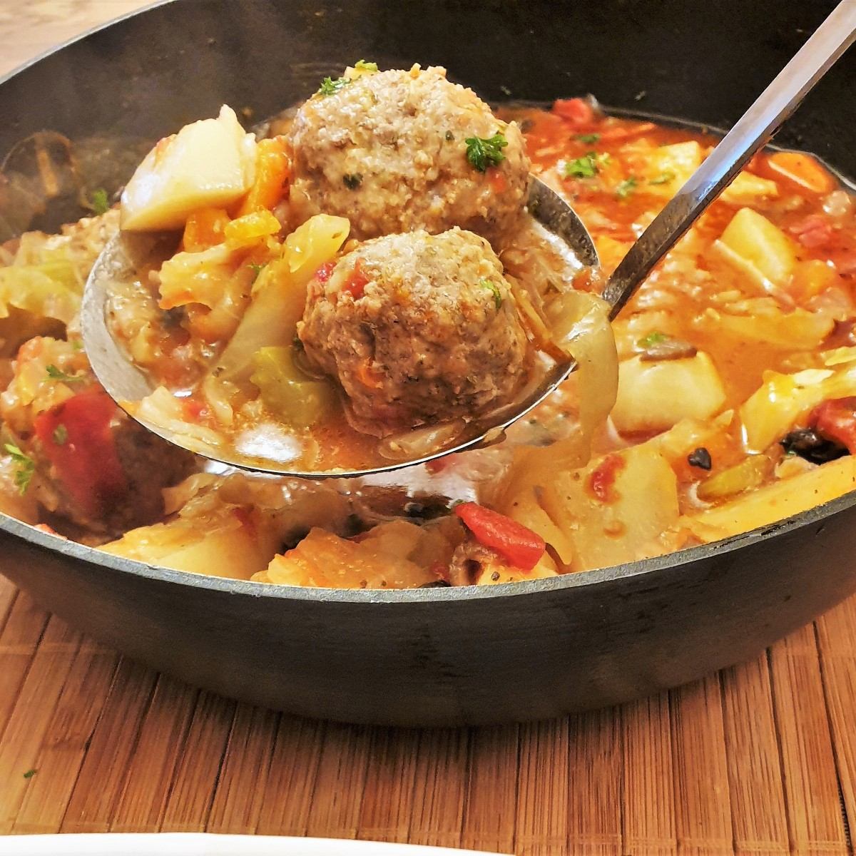 Meatballs being spooned from a pan of meatball and vegetable soup.