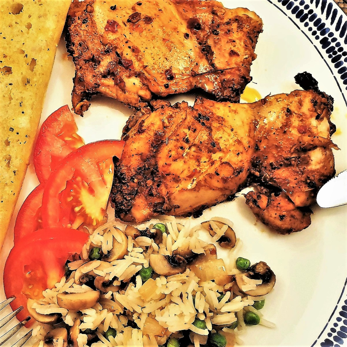 Two peri peri chicken thighs on a white plate with rice, tomatoes and garlic bread.