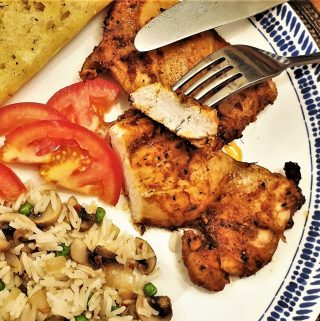 Two chicken thighs on a plate with tomatoes, mushroom rice and garlic bread.