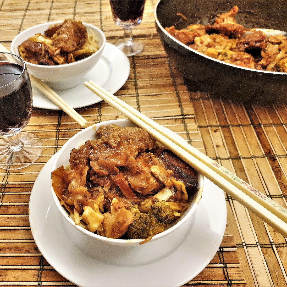 A bowl of szechual chicken with chopsticks in the foreground with a wok of chicken in the background