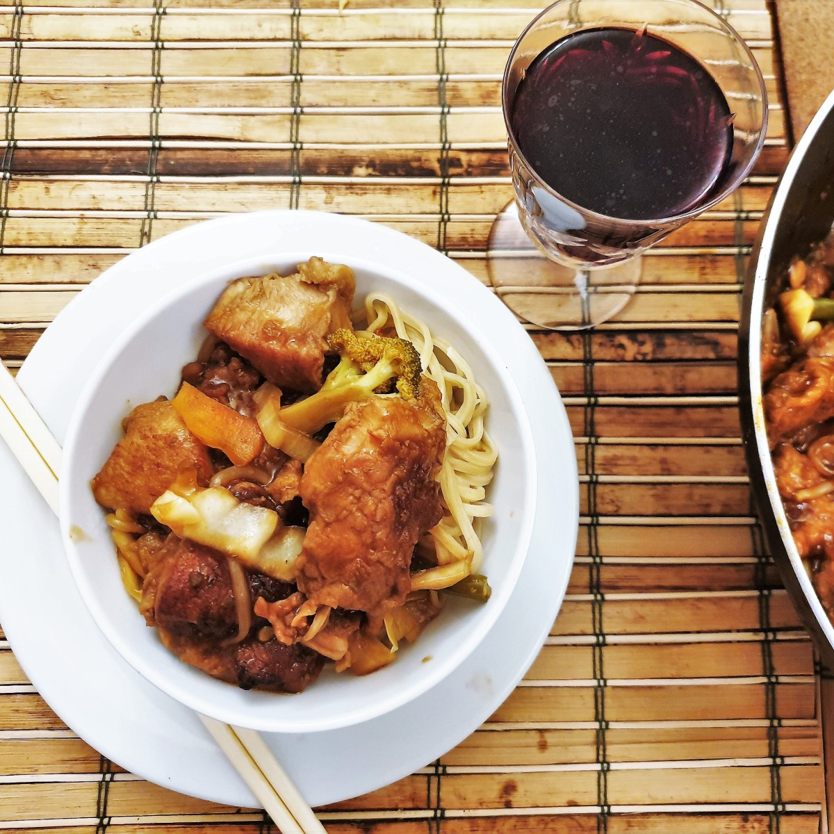 Overhead shot of a bowl of szechuan chicken next to a glass of red wine.