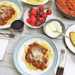 Overhead shot of a table set with plates of spaghetti bolognese.