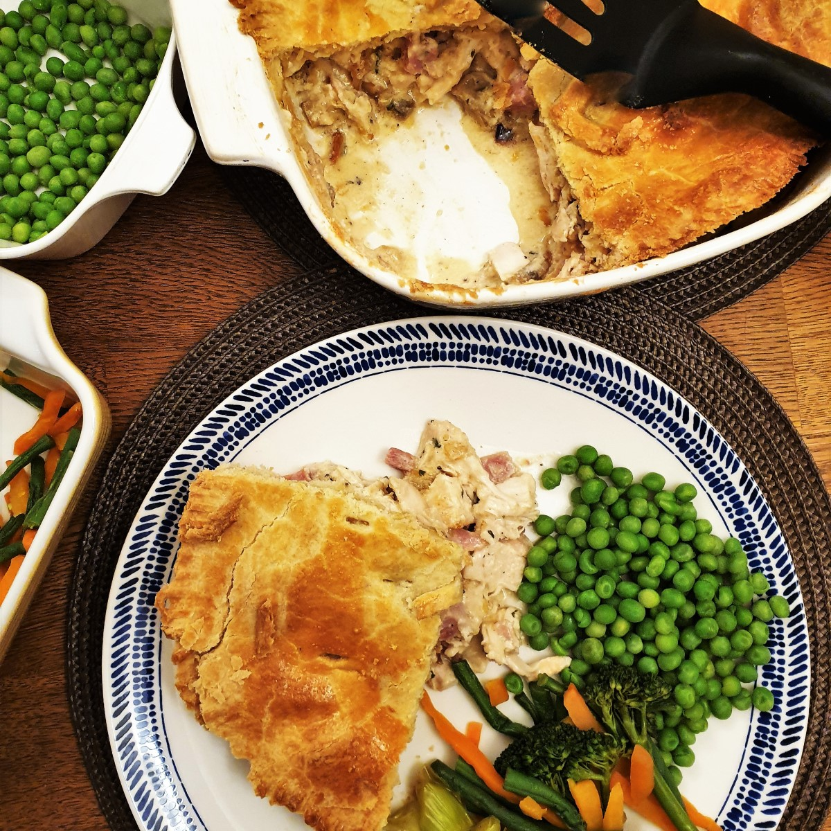 Overhead shot of a plate of chicken and ham pie  with vegetables, next to the dish of pie with a slice removed..