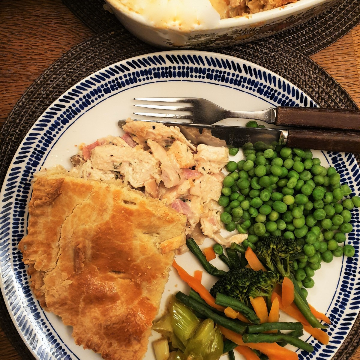 A plate of chicken and ham pie with vegetables,