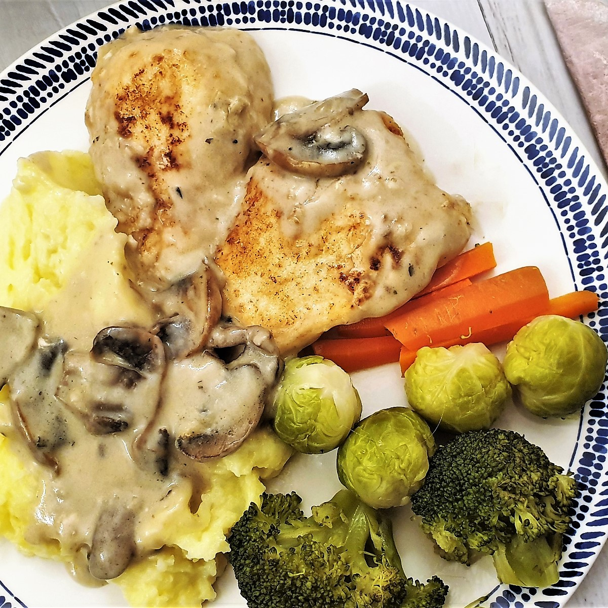 A plate of creamy chicken marsala with mushrooms, mashed potatoes and vegetables.