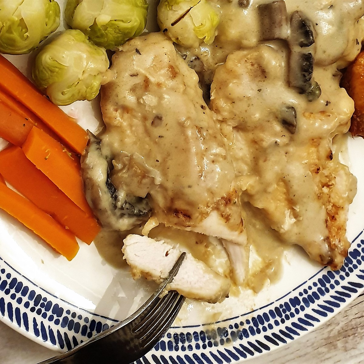 Close up of a piece of chicken marsala showing the inside of the chicken.
