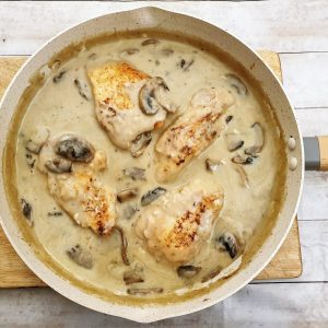 Chicken fillets cooking in marsala sauce in a frying pan.
