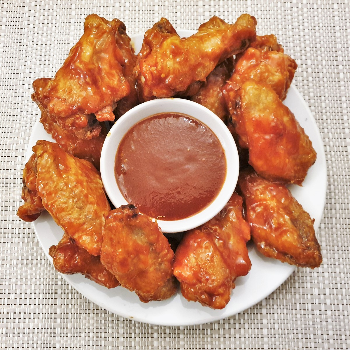 A plate of chicken wings surrounding a bowl of barbeque sauce.