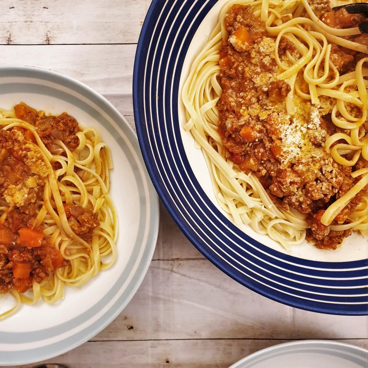 Two bowls of lamb ragu over pasta.