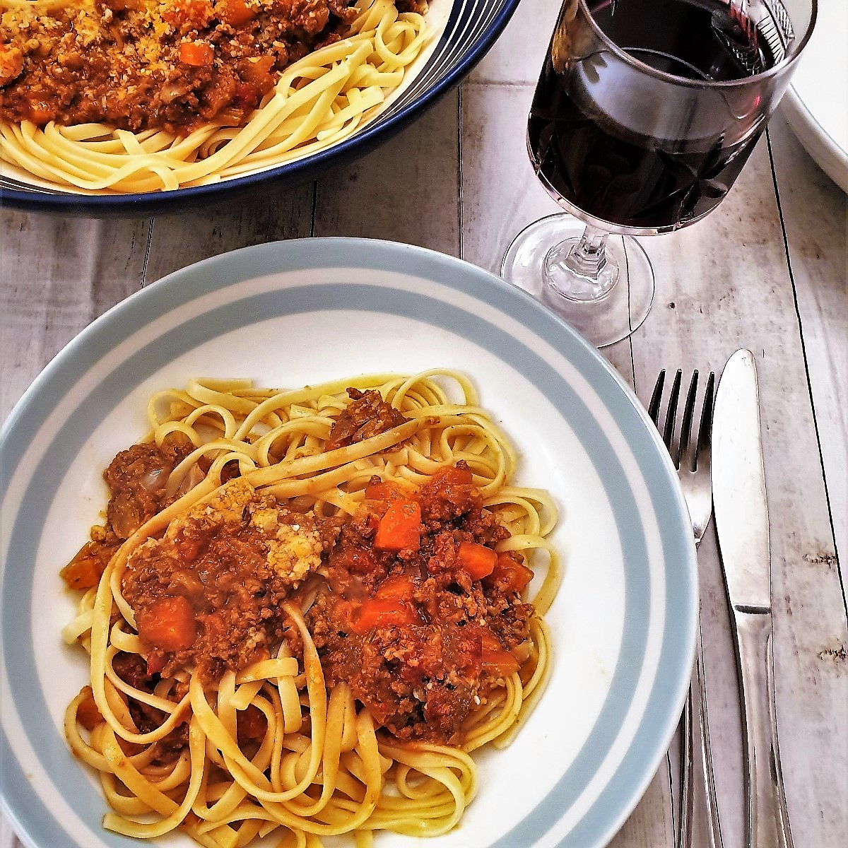 A bowl of lamb ragu on a bed of linguine.