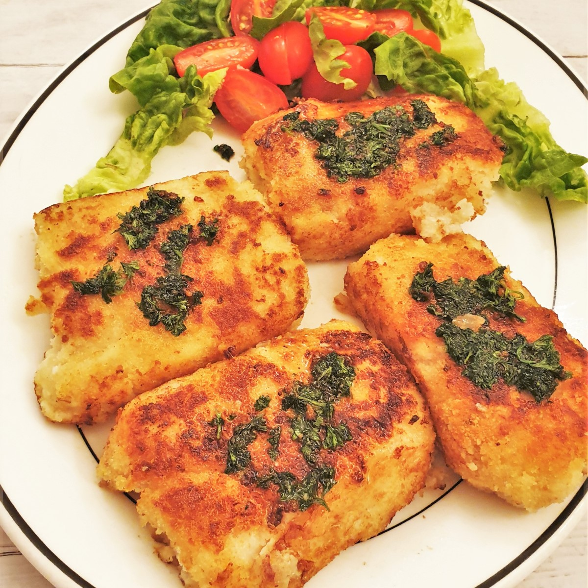 4 fillete of crispy fried fish on a plat, covered with parsley sauce.