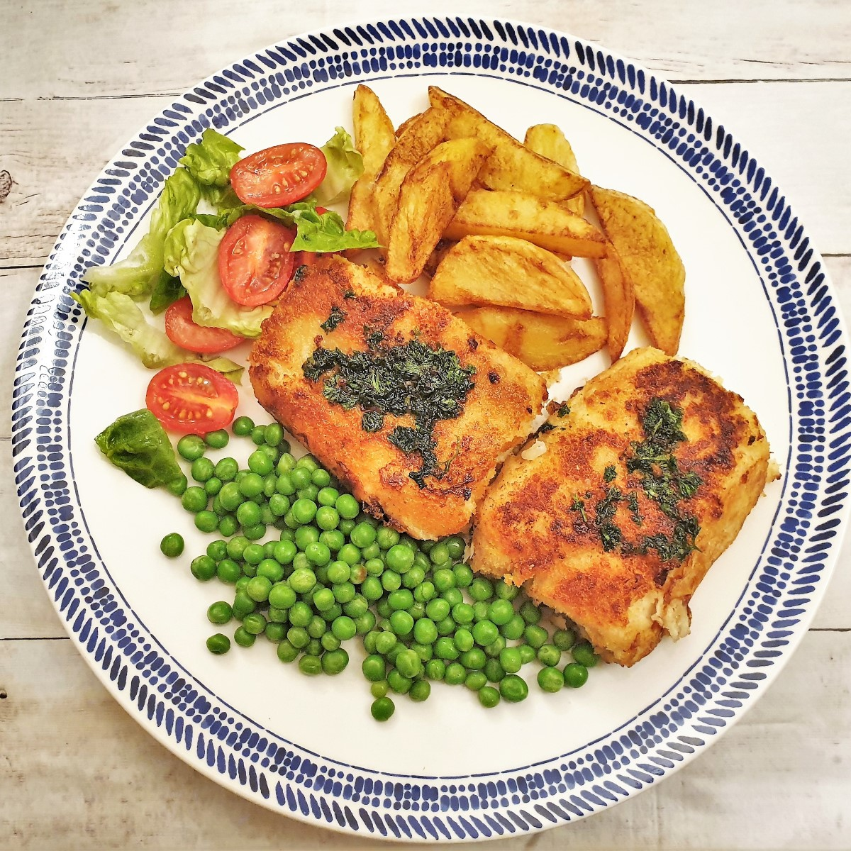 Overhead shot of fried fish fillets on a plate with chips, peas and tomato salad.