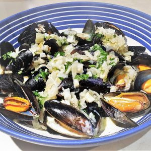 A dish of mussels covered in creamy garlic and onion sauce.