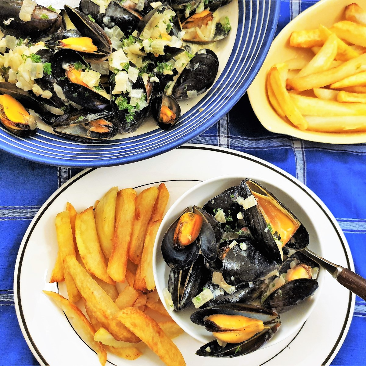 A dish of open mussels on a plate with french fries alongside a serving dish filled with cooked mussels.