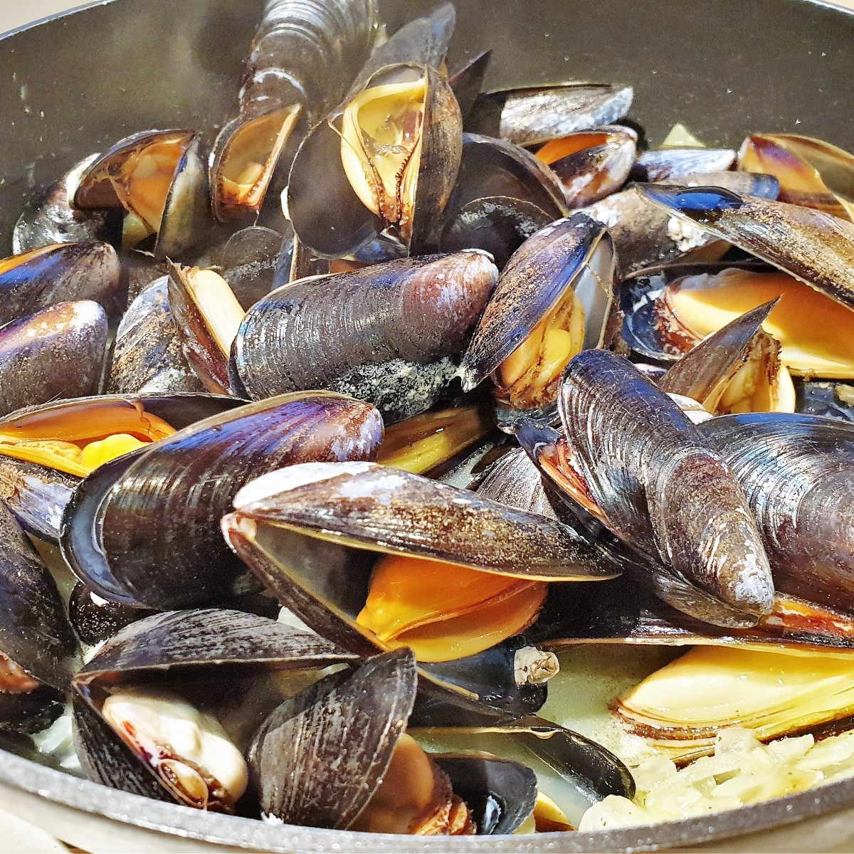 A pan of freshly cooked mussels, all opened to reveal the delicacy inside.