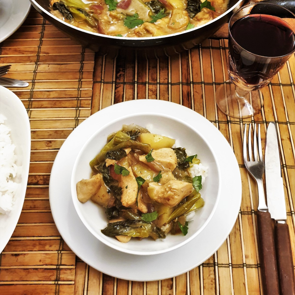 A table set with a bowl of thai green curry next to a dish of jasmine rice.