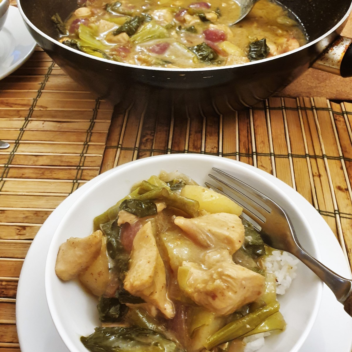 A bowl of thai green chicken curry on the table next to a wok.