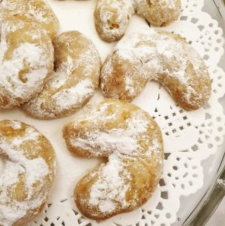Walnut crescent cookies on a doily.