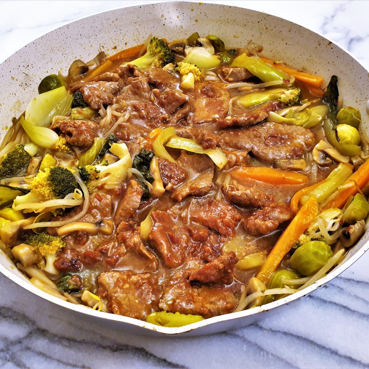 Side-on shot of a pan of garlic beef in oyster sauce with vegetables.
