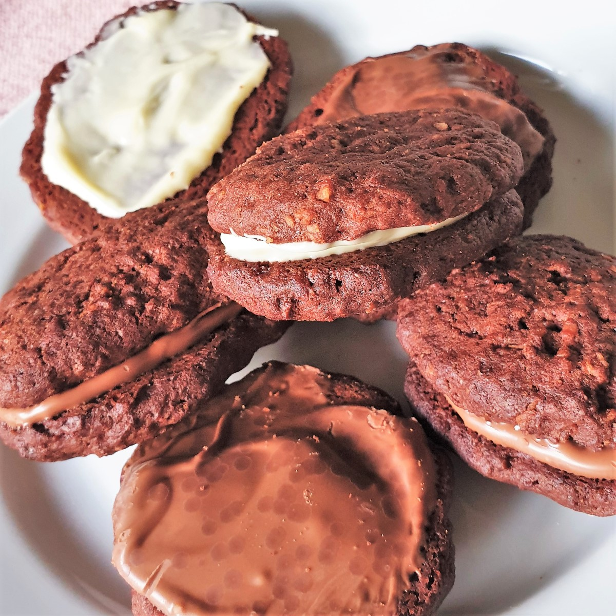 Romany creams on a plate, some sandwiched together with chocolate, others just spread with chocolate.