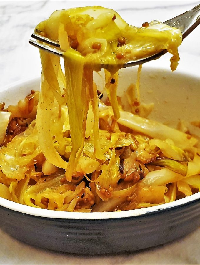 A dish of buttered cabbage and leeks with mustard seeds.