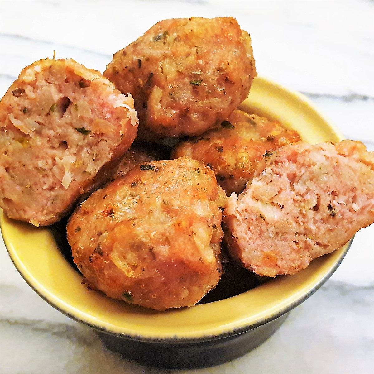 A bowl of sausagemeat stuffing balls with one cut in half.