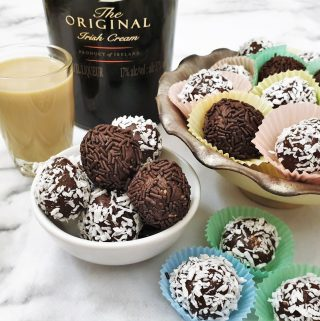 A dish of chocolate truffles, rolled in coocnut and chocolate sprinkles, in front of a bottle of Baileys.