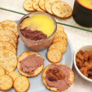 A dish of chicken liver pate with biscuits.