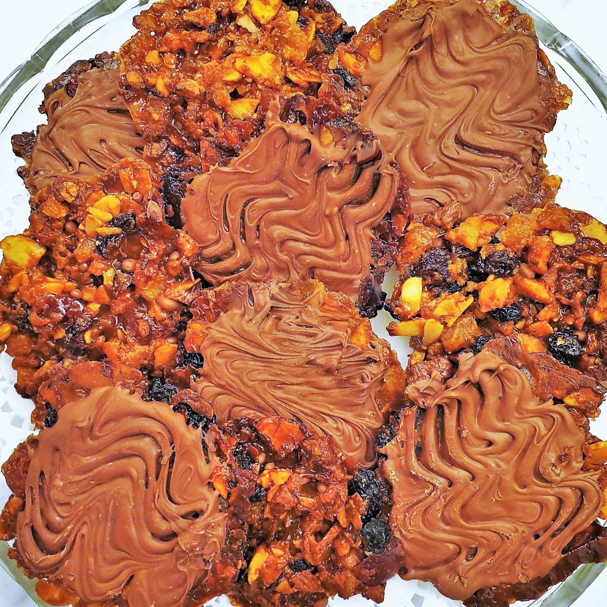 Chocolate coated florentines on a glass plate.