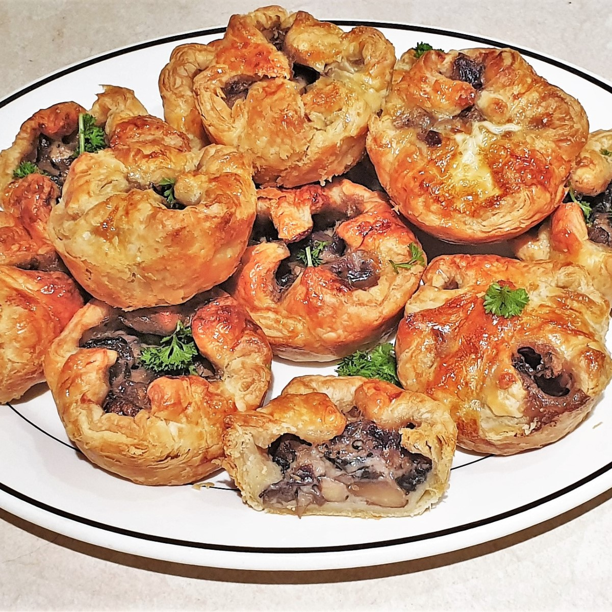 A serving dish piled with mushroom tarts.