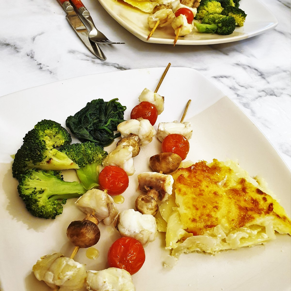 Monkfish skewers on a plate with vegetables.