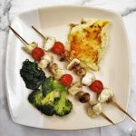 Two monkfish kebabs on a plate with vegetables and potatoes.